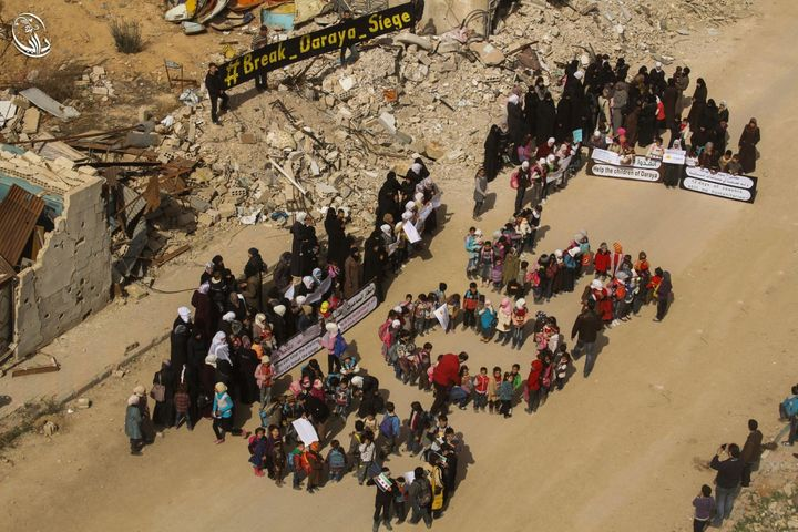 Dozens of people in Daraya, a besieged Syrian town, appealed for international help through a massive SOS sign and placa