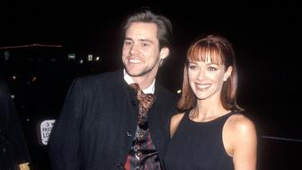 """HOLLYWOOD - DECEMBER 6:   Actor Jim Carrey and actress Lauren Holly attend the """"Dumb and Dumber"""" Hollywood Premiere on December 6, 1994 at the Pacific's Cinerama Dome in Hollywood, California. (Photo by Ron Galella, Ltd./WireImage)"""