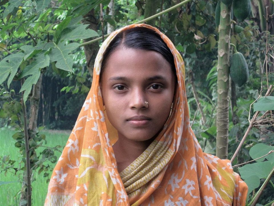 Rina Begum, 14, stands outside her parents' home, in Jamalpur, Bangladesh. Rima, whose education was cut short at Grade 6, wa