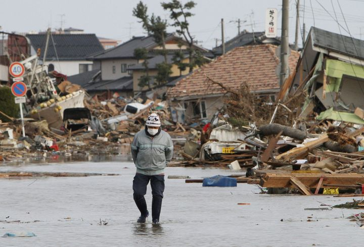 A man looks for the remains of his house, which was destroyed by the tsunami, at Watari town in Miyagi prefecture on March 14