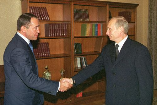 Mikhail Lesin shakes hands with Russian President Vladimir Putin. A medical examiner has determined Lesin died of blunt force
