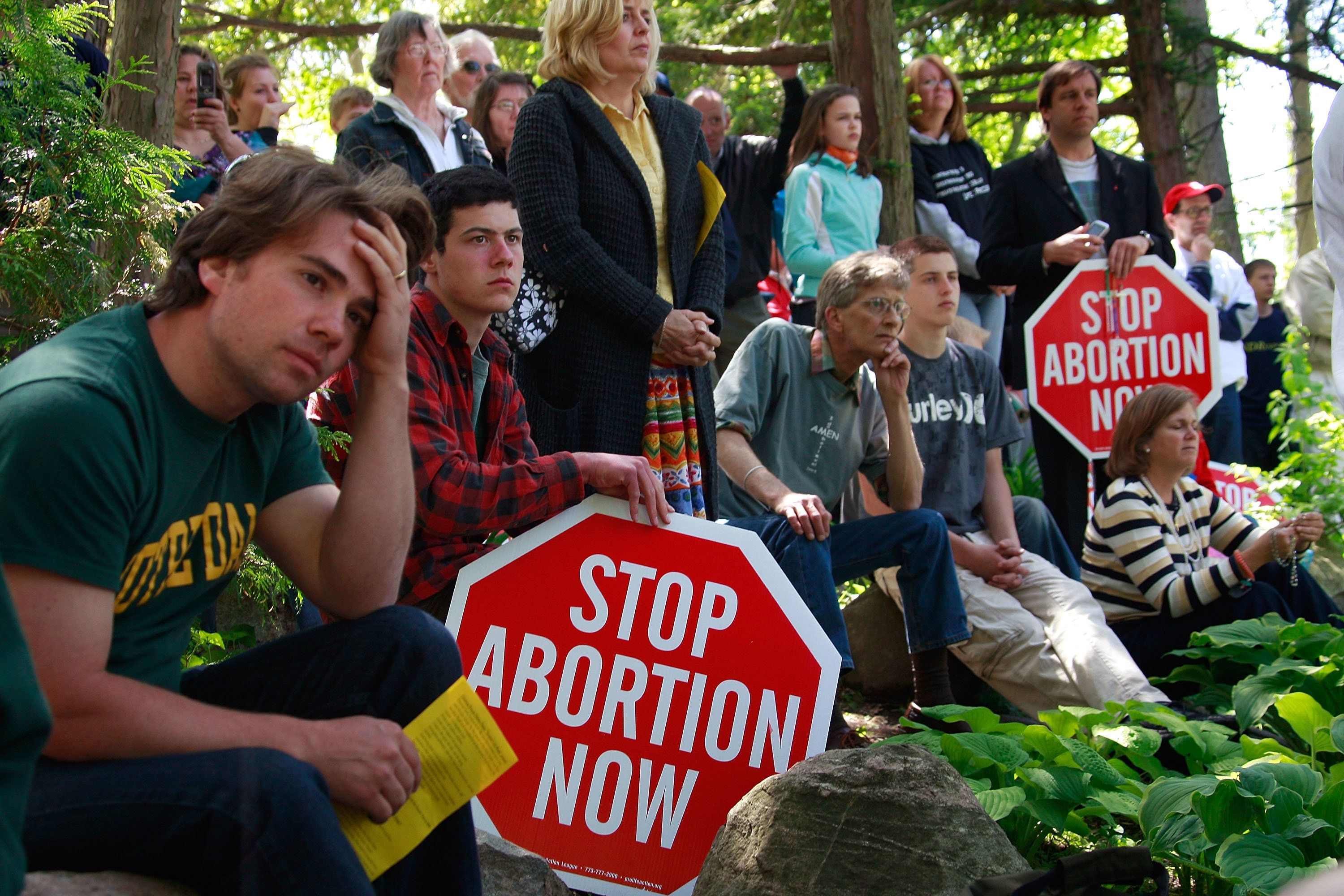 SOUTH BEND, IN - MAY 17: Pro-life activists look on as Notre Dame University students hold an alternative commencement cermony held to protest President Barack Obama's visit to the Grotto of Our Lady of Lourdes on the campus of Notre Dame University May 17, 2009 in South Bend, Indiana. Students chose to skip the commencement after the school decided to invite President Obama, who supports abortion rights, to deliver the commencement address and award him an honorary degree. (Photo by Scott Olson/Getty Images)