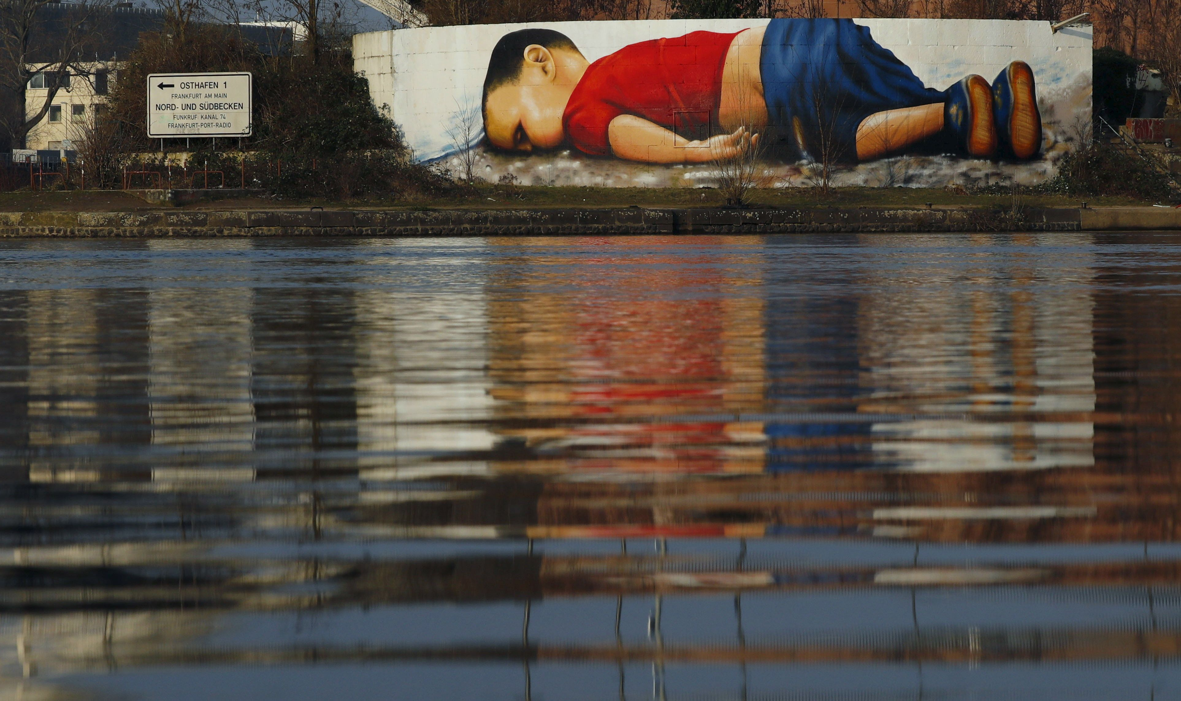 A huge mural painting showing Syrian tot Aylan Kurdi on the Main River in
