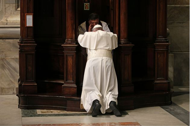 Pope Francis confesses during the penitential celebration in St. Peter's Basilica at the Vatican City,...