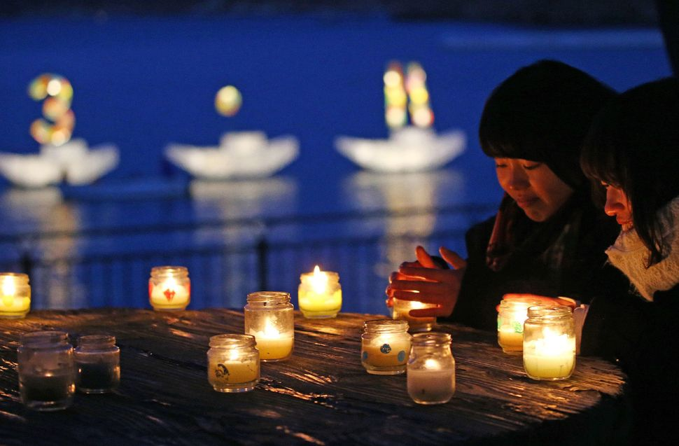 "People pray for the earthquake and tsunami victims as candle boats display ""3.11"" -- for March 11, the day the earthquake str"