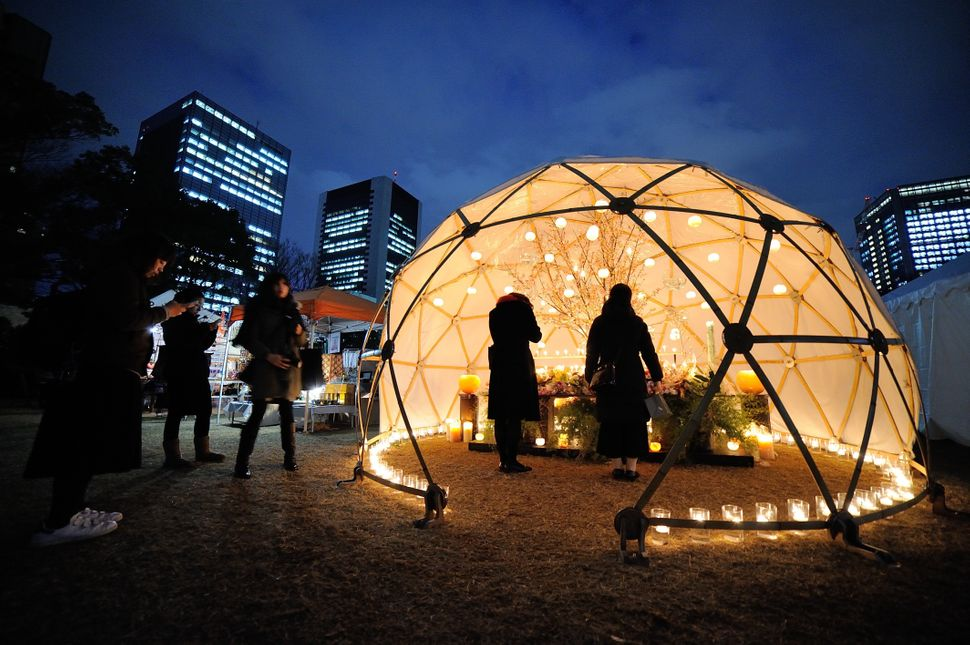 People pray in a lighted dome in Tokyo.