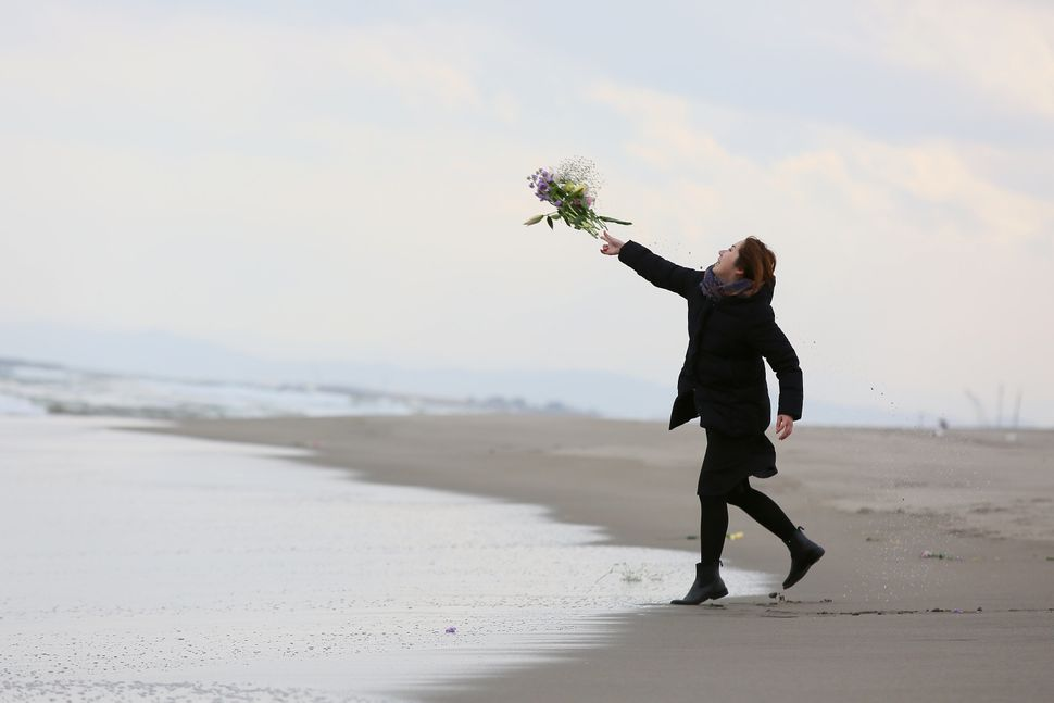 A woman throws flowers into the sea at Fukanuma beach in Sendai, a city in the Tohoku region.