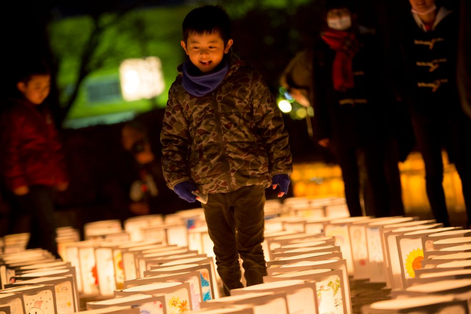 A boy walks among paper lanterns marking the fifth anniversary of the Tohoku earthquake in Natori, a city along Japan's east
