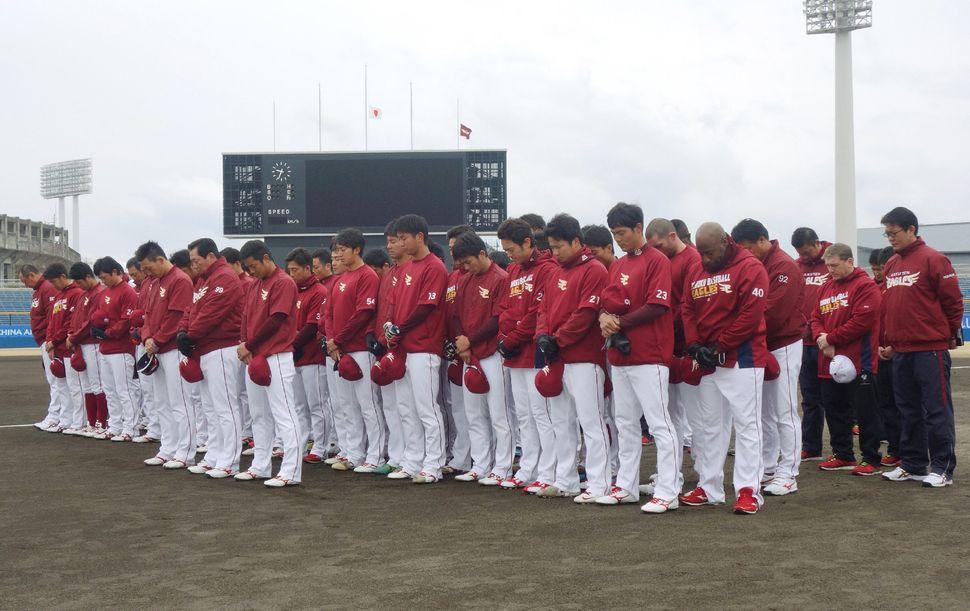 The Tohoku Rakuten Eagles baseball team observes one minute of silence at a baseball stadium in Shizuoka prefecture.