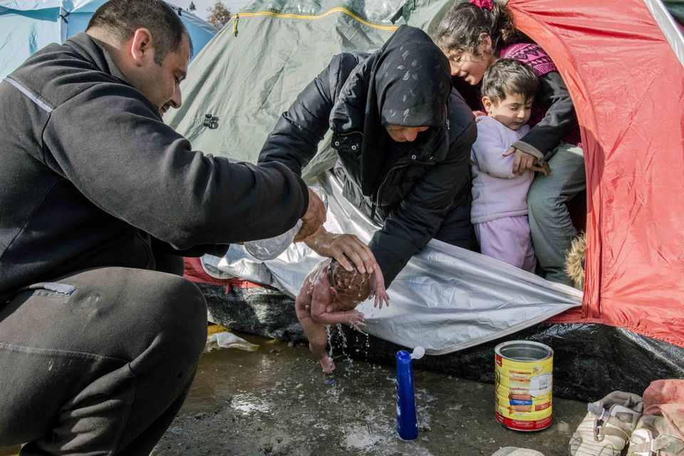 A photo showing refugees washing a newborn baby in the makeshift refugee camp in Idomeni, Greece, has...