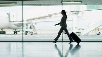 Businesswoman with suitcase in airport