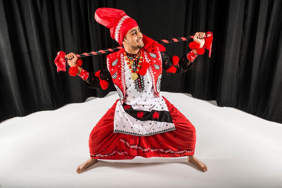 "CU Bhangra dancer Ishaan Kolluri squats low, with a large wooden stick known as a ""koonda"" balanced on his shoulders."