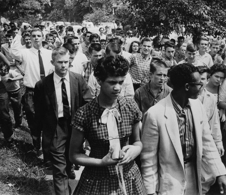 Dorothy Counts-Scoggins getting escorted out of Harding High School in 1957 as a crowd of students follows.