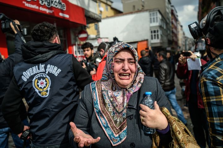 A woman cries as Turkish anti-riot police officers disperse supporters in front of the headquarters of the Turkish daily news