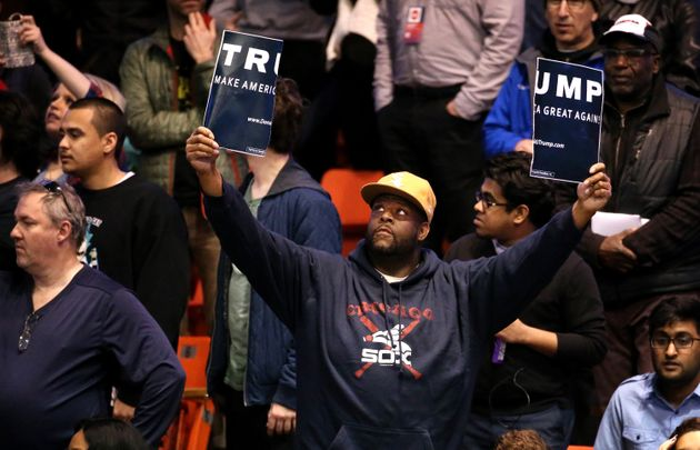 A protestor holds a ripped Donald Trump sign up before the start of a rally for the Republican presidential...