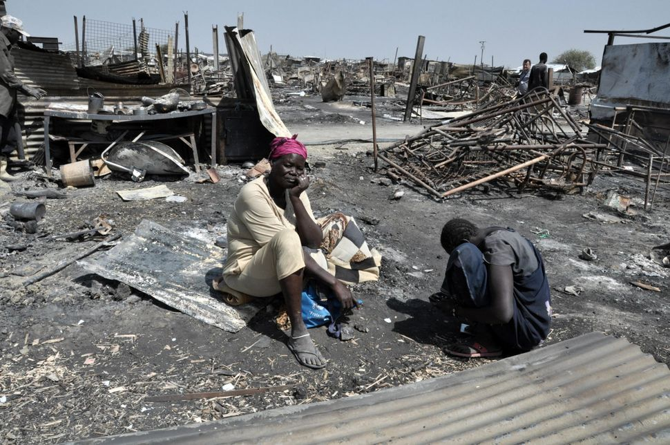 Displaced women sit in the ashes of their shelter, which was burned during the fighting and fires on Feb. 17 and 18
