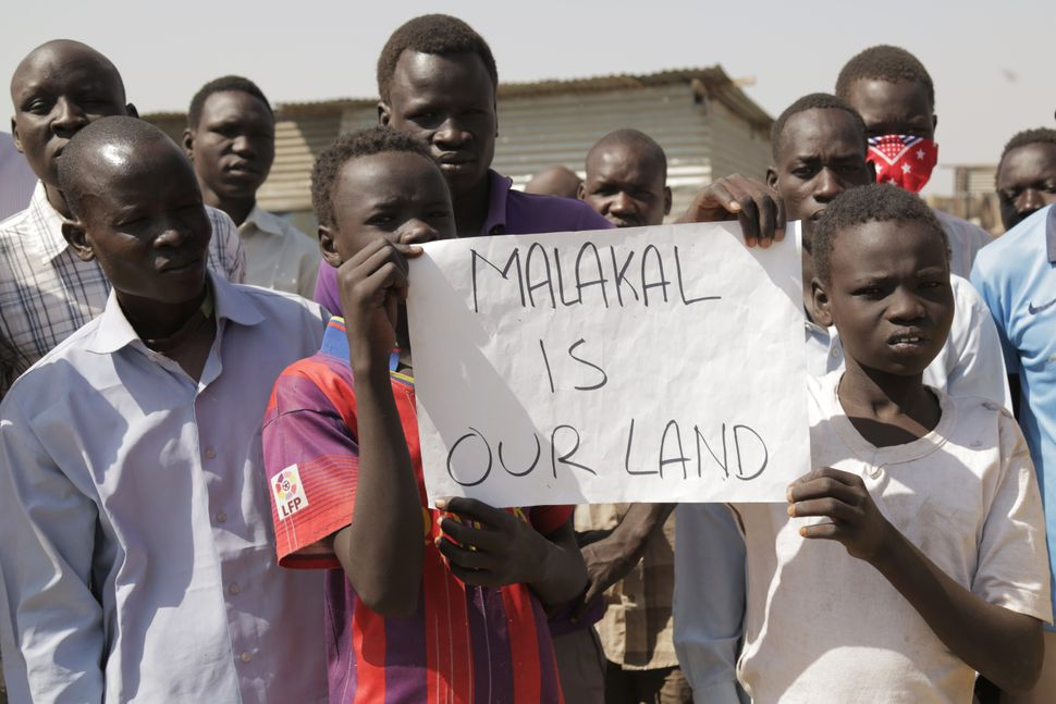 Demonstrators hold signs as the United Nations convoy visiting Malakal passes by on Feb. 26.
