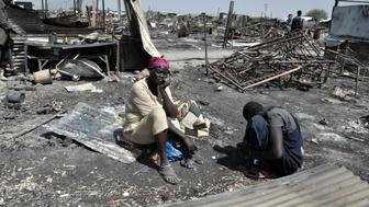 Displaced women sit in the ashes of their shelter which was burnt during the fighting and fires on 17 and 18 February in the UN Protection of Civilians (PoC) site in Malakal.