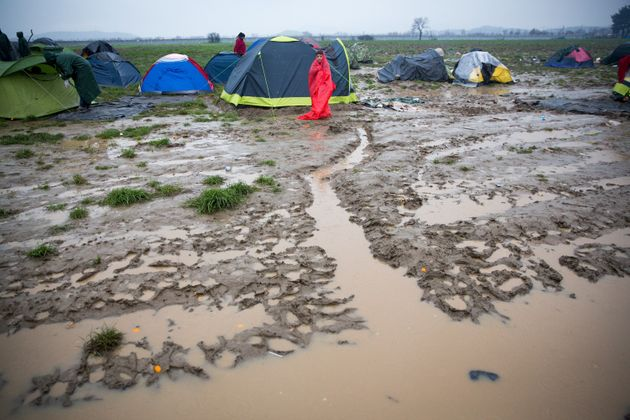 A boy stands besides his tent as rain falls at the Idomeni refugee camp on the Greek Macedonia border...
