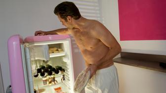 Topless mid adult man with frozen pizza standing in front of open fridge