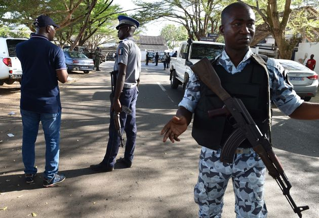Ivorian armed forces take position as people leave the beach after heavily armed gunmen opened fire on...