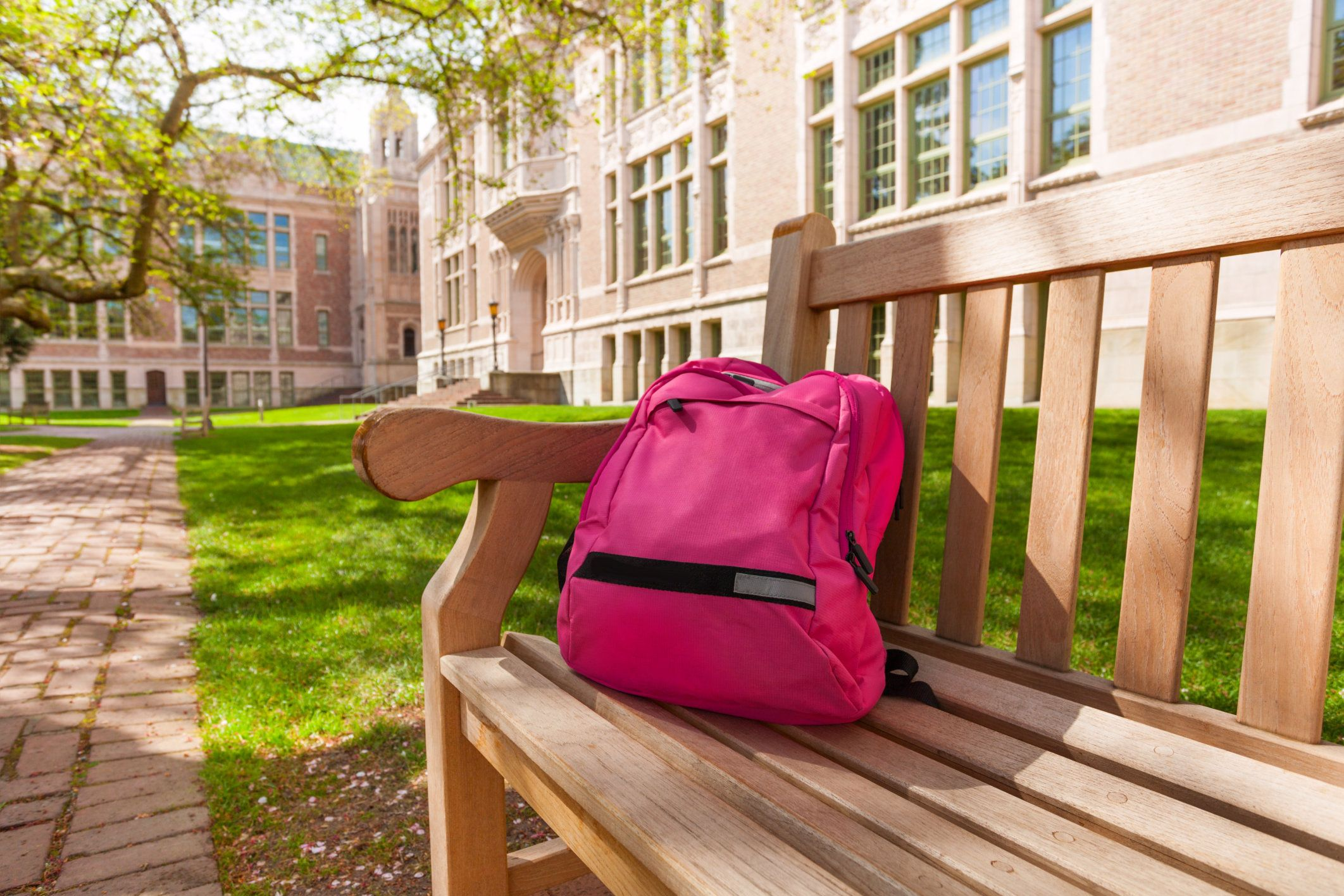 Backpack laying on the bench with educational buildings on the background after classes