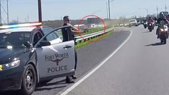 As the motorcyclists pass the officer is seen spraying some kind of aerosol in their direction.