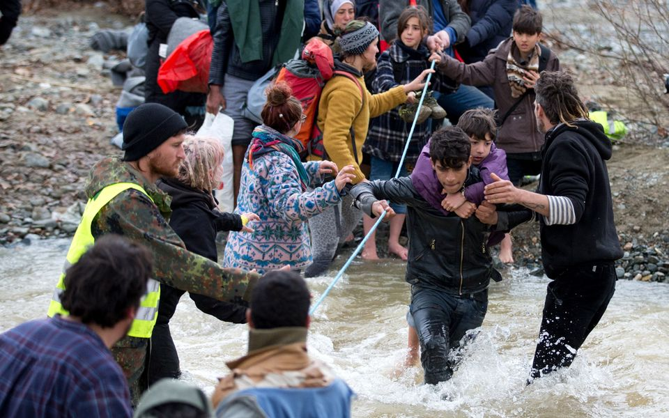 Migrants try to cross a river after leaving the Idomeni refugee camp, on March 14, 2016 in Idomeni, Greece.