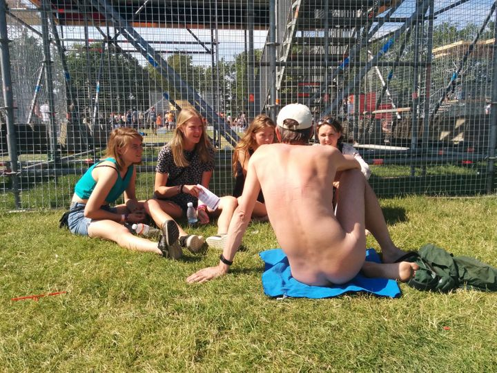 Nudist talking to women at an event.