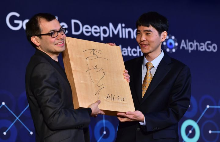 Lee Se-Dol (R), one of the greatest modern players of the ancient board game Go, presents the 'Go' game board with his signat