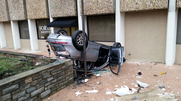 Glass and debris surround a vehicle that fell four stories from a parking garage.