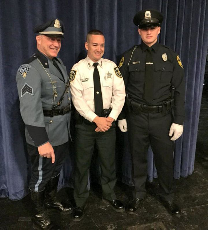 Deputy John Robert Kotfila Jr. poses with his father, Massachusetts State Police Sgt. John R. Kotfila Sr., left, and his brot