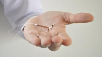 Holding an IUD birth control copper coil device in hand, used for contraception - front view