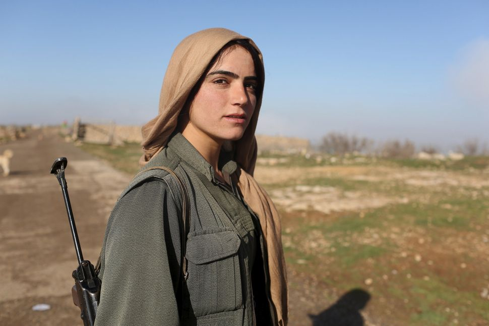 A female Kurdistan Workers Party fighter stands near a security position in Sinjar, Iraq on March 13, 2015. Similar to their