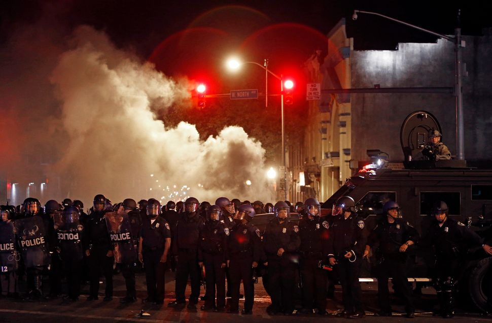 During the Baltimore riots in 2014, police attempt to disperse a group of media and civilians after the 10 p.m. curfew a