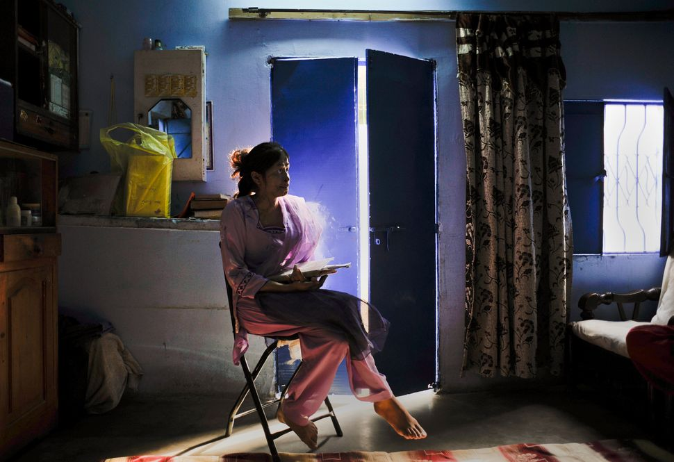 Memoona, a 23-year-old survivor of an acid attack, poses for a photograph inside her home in Karachi, Pakistan on Decemb