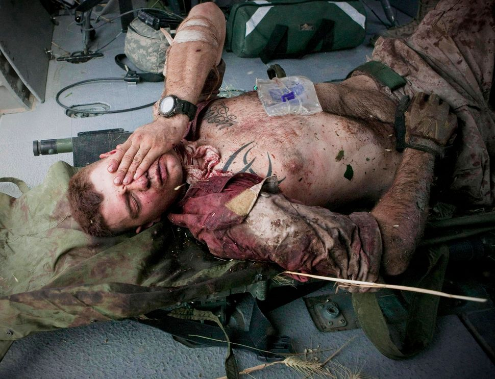 On June 4, 2011, injured U.S. Marine Cpl. Burness Britt reacts after being lifted onto a medevac helicopter. German photograp