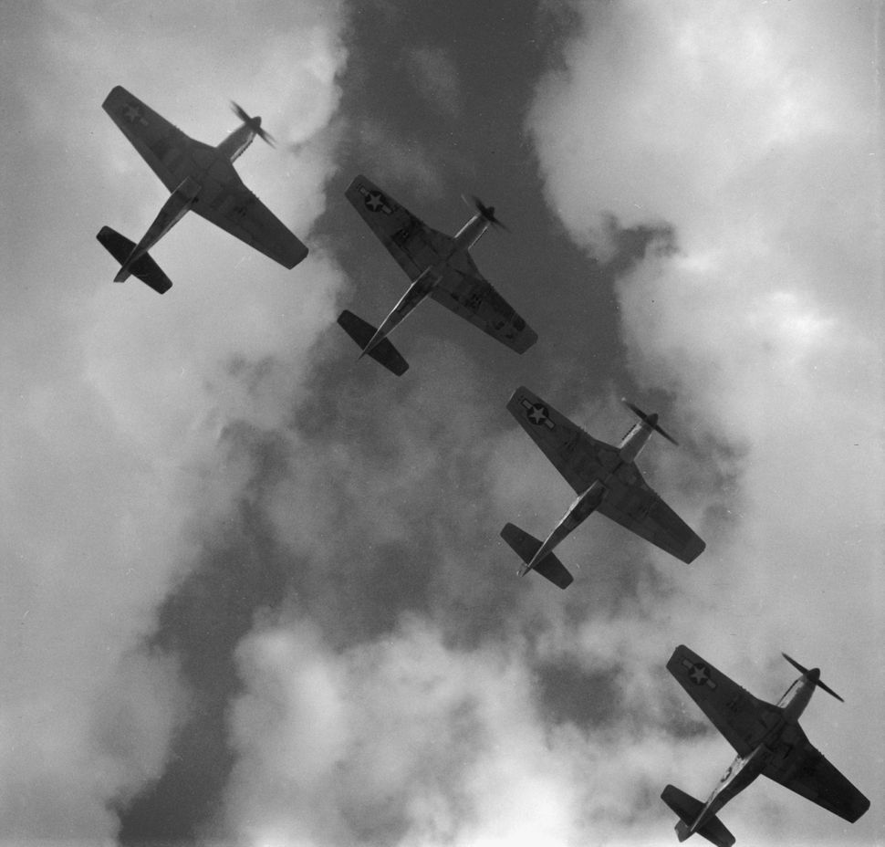 View from below of four P-51 Mustangs flying in formation, near Ramitelli airbase in Italy in March of 1945.
