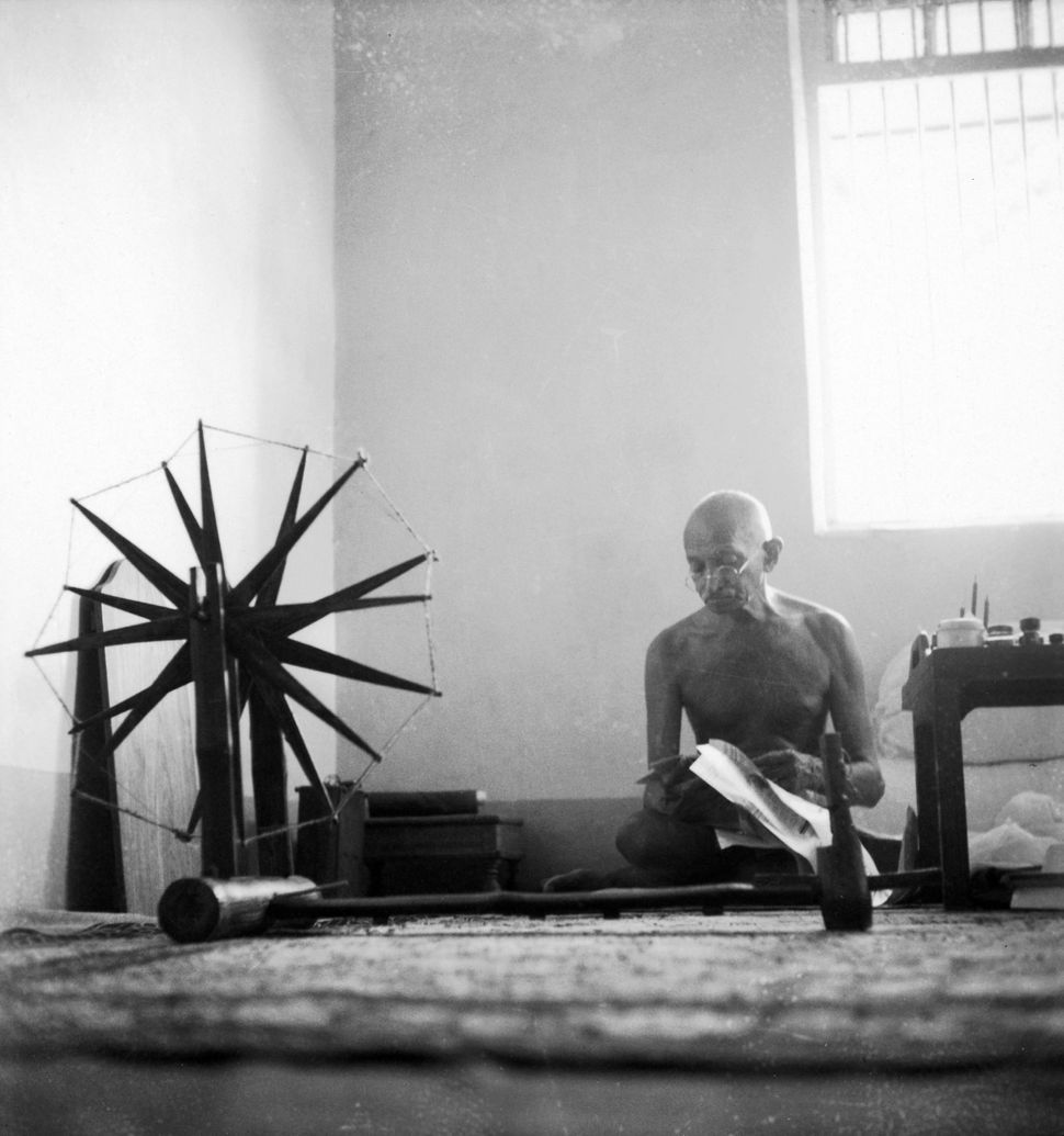 Indian leader Mohandas Gandhi reads as he sits cross-legged on floor next to a spinning wheel which looms in the foregro