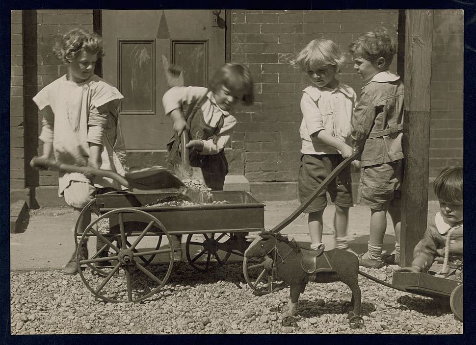 Four young children load rocks into a wagon while a smaller chid sits on the ground playing with his toy pony cart in 19