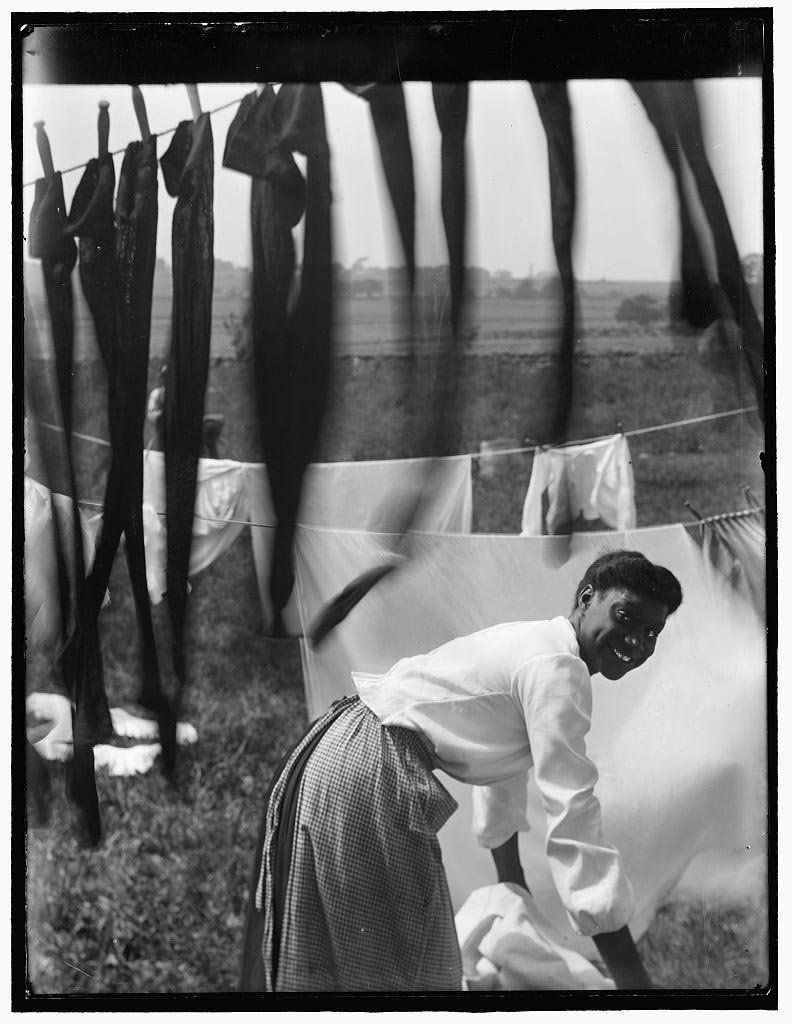 A young African American woman working in the midst of clotheslines heavy with sheets and stockings in Newport, Rhode Island