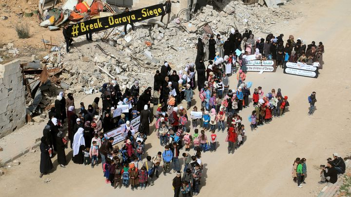 People protest in the besieged town of Daraya, Syria. More than 12 million people in the country still do not have