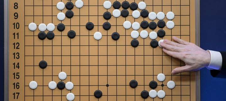 A commentator in a media room positions pieces forming a replica of a game between 'Go' player Lee Se-Dol and the Google-deve