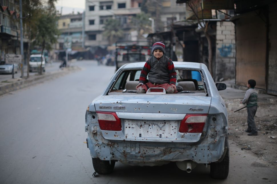 A child sits on a car destroyed by an explosion in Ghouta, Syria.