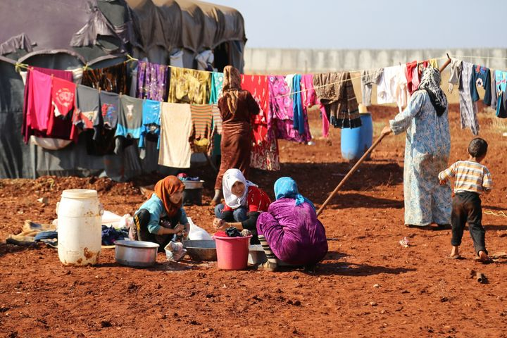 Women and children wash their clothes at a camp in Idlib, Syria. Almost 1 million people were forced to flee their homes in 2