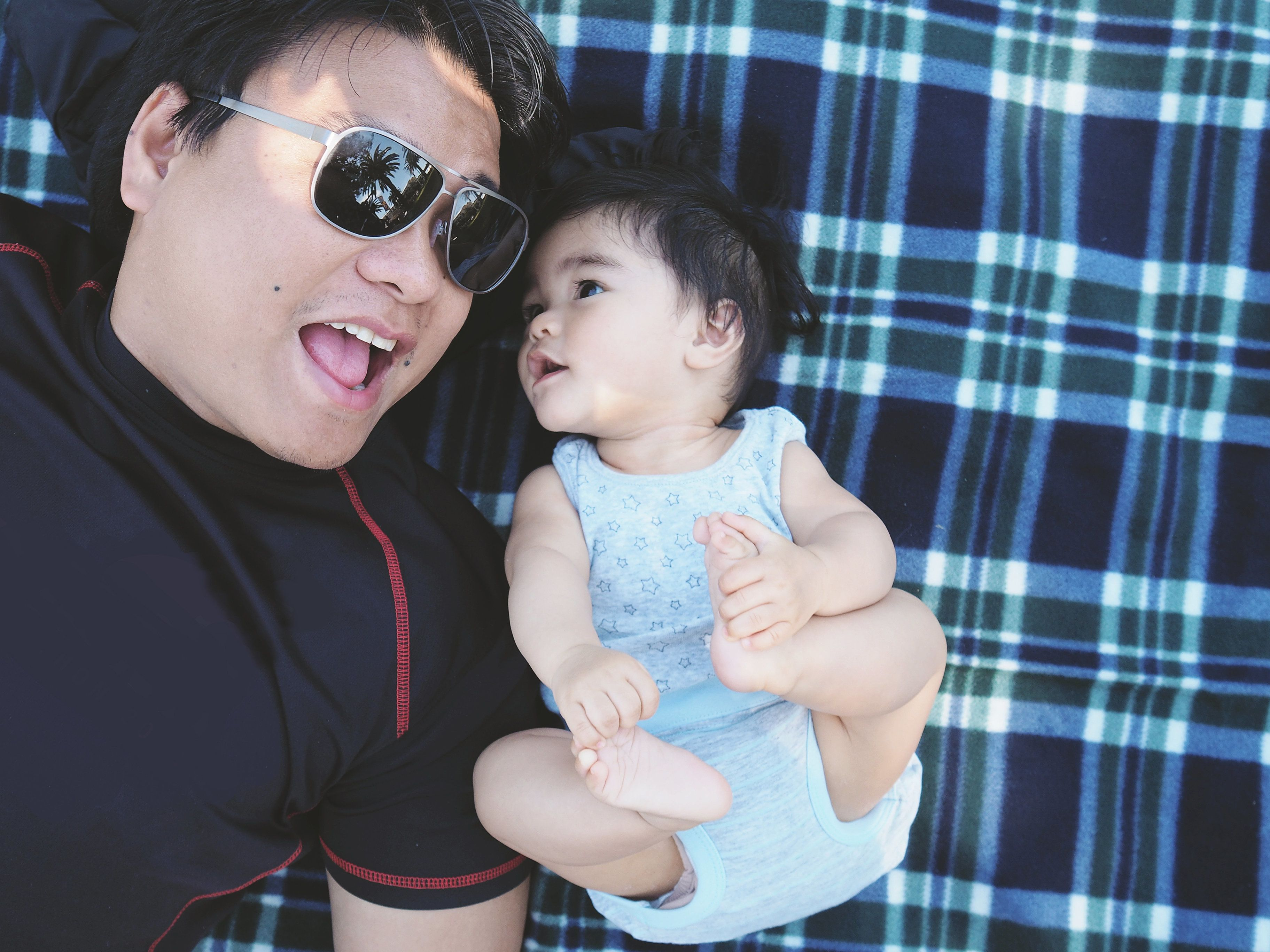 Asian Filipino Dad and baby boy (son) both lie on their backs on a picnic blanket. Dad is wearing shades and seems to be talking to his baby. Baby is looking directly at his dad while holding or touching both his feet.