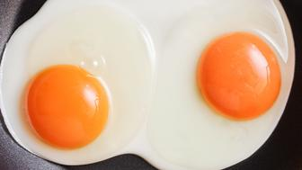 Two fresh eggs being fried in a non-stick pan
