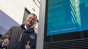 EAST 16TH STREET AT THIRD AVENUE, NEW YORK, NY, UNSPECIFIED - 2016/02/18: Mayor de Blasio gives gives a 'thumbs up' after speaking with a 311 operator during a test of the system before the press conference. Mayor Bill de Blasio announced the launch of the LinkNYC public WiFi and communications network that will be implemented throughout New York City with the unveiling of the first of 7500 terminal kiosks on Third Avenue at East 16th Street; and responded to questions from members of the press regarding the data that will be collected by the system, privacy concerns, and the potential use of the kiosks as surveillance devices. (Photo by Albin Lohr-Jones/Pacific Press/LightRocket via Getty Images)