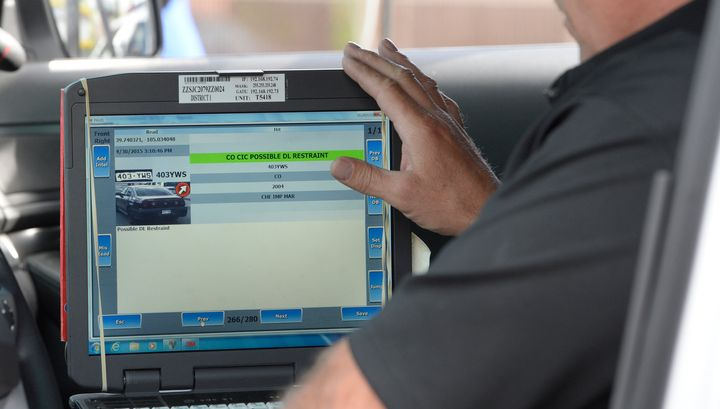 A Denver police officer shows off technology that scans license plates to see if cars might have been involved in crimes or i