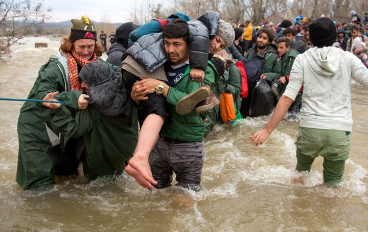Migrants try to cross a river after leaving the Idomeni refugee camp on March 13, 2016, in Greece. Onemillion migrants